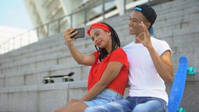 Multi-ethnic teenagers making selfie and having fun sitting on stairs outdoor. Stock footage stock video footage