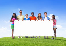 Multi-Ethnic Teenagers Outdoors Holding Billboard for Copy Space. Multi-Ethnic Teenagers Outdoors Holding Empty Billboard for Copy Space Stock Photo
