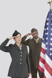 Multi-ethnic US military officers saluting American flag over gray background Stock Photos
