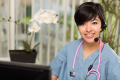 Multi-ethnic Woman Wearing Headset and Stethoscope royalty free stock photography