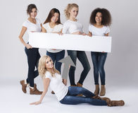 Multi ethnic women with empty board Royalty Free Stock Image