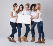 Multi ethnic women with empty board Stock Photo