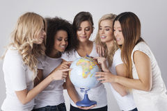 Multi ethnic women with globe Stock Photography