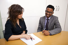 Multi-ethnic work colleagues looking at paperwork on a table Stock Photo