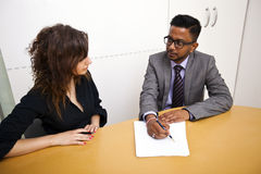 Multi-ethnic work colleagues signing paperwork on a table Royalty Free Stock Images