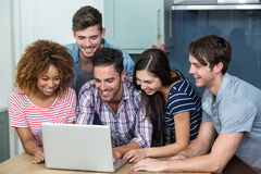 Multi-ethnic young friends looking in laptop on table Stock Photography