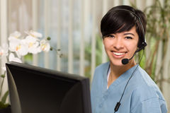 Multi-ethnic Young Woman With Headset and Scrubs. Smiling Attractive Multi-ethnic Young Woman Wearing Headset and Scrubs Near Her Computer Monitor stock photos