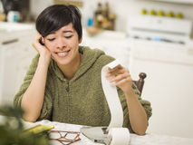 Multi-ethnic Young Woman Smiling Over Financial Calculations Royalty Free Stock Images