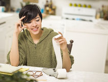 Multi-ethnic Young Woman Smiling Over Financial Calculations stock photos