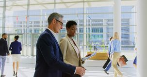 Multi ethnics business people discussing over digital tablet in the office lobby 4k. Side view of multi ethnic business people discussing over a digital tablet stock footage