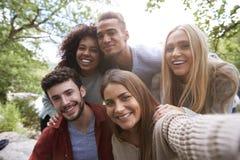 Multi Ethnie von fünf jungen erwachsenen Freunden werfen zur Kamera beim Nehmen eines selfie während eines Bruches in einer Wande lizenzfreie stockbilder