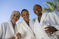 Multi ethnische Freunde beim Bademantel-Lächeln Stockfotografie