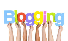 Multi ethnische Leute, die das Blogging Wort halten Stockbild