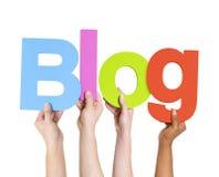 Multi ethnische Leute, die das Wort-Blog halten Stockbild