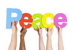 Multi ethnische Leute, die den Wort-Frieden halten Stockfoto