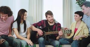 Multi etnici degli amici felici ed attraenti godono insieme del tempo in un grande salone essi che giocano su una chitarra che ca video d archivio