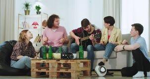 Multi etnici degli amici molto attraenti ed artistici godono insieme del tempo mentre le cantano su una chitarra che spendono un  archivi video