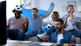 Multi-etnisch Argentijns vrienden het letten op spel op TV die thuis, doel vieren stock afbeeldingen