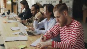 Multi-etnisch geconcentreerd team van medewerkers die aan technologie startproject in openspacebureau werken Jonge hipstermens stock video