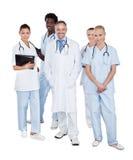 Multi-etnisch medisch team die zich over witte achtergrond bevinden Royalty-vrije Stock Foto's