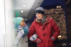 Multi-etnisch paar die bij schemer tijdens de winter converseren stock afbeeldingen