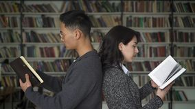 Multi etnisch paar die het rijtjes wegknippen bevinden zich door boeken in bibliotheek stock footage