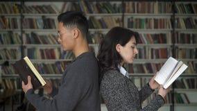 Multi etnisch paar die rijtjeslezing in bibliotheek bevinden zich stock video