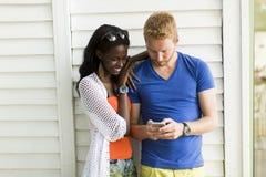 Multi-etnisch paar met smartphone bij de zomer royalty-vrije stock fotografie