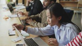 Multi-etnisch team van medewerkers die bij lijst zitten die aan startproject werken Het Aziatische geconcentreerde vrouw typen op stock videobeelden