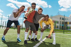 Multi-etnisch voetbalteam met drinkbeker die zich op voetbalhoogte bevinden Stock Afbeeldingen