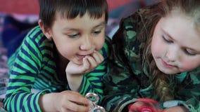 Multi-etnisch Weinig jongen en meisjes het spelen met de spinner die op de laag 4K liggen stock footage