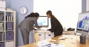 Multi-etnische bedrijfscollega's die over grafieken over grafieken gaan Stock Foto