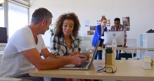 Multi-etnische bedrijfscollega's die over laptop in modern bureau 4 4k bespreken stock footage