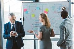 multi-etnische bedrijfsmensen die bij whiteboard werken terwijl hogere zakenman royalty-vrije stock afbeelding