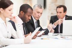 Multi etnische bedrijfsmensen die het werk bespreken Stock Foto