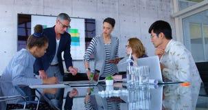 Multi-etnische bedrijfsmensen die over blauwdruk in de conferentieruimte op modern kantoor 4 4k bespreken stock footage