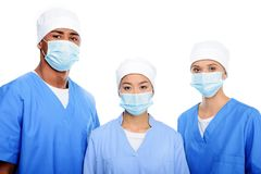 multi-etnische chirurgen in medische maskers en kappen, stock foto