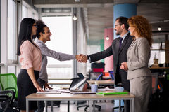 Multi-etnische commerciële teams bij vergaderzaal het schudden handen stock foto
