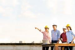 Multi-etnische diverse groep die ingenieurs of partners bij bouwwerf, exemplaar op ruimte op hemel richten tijdens zonsondergang Royalty-vrije Stock Afbeeldingen