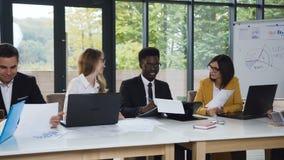 Multi-etnische groep bedrijfsmensen die bij lijst zitten die ideeën delen terwijl commerciële vergadering in modern bureau creati stock videobeelden