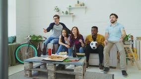 Multi etnische groep die de ventilators van vriendensporten sport op gelijke op TV letten die samen snacks thuis eten en bier dri stock video