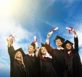 Multi etnische groep gediplomeerde studenten stock fotografie