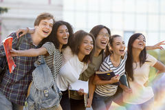 Multi-etnische groep jonge gelukkige studenten die zich in openlucht bevinden stock afbeeldingen
