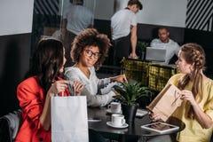 multi-etnische groep jonge vrouwen met het winkelen zakken royalty-vrije stock afbeeldingen