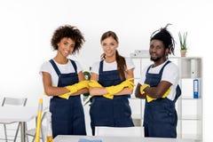 multi-etnische groep professionele reinigingsmachines in rubberhandschoenen die zich met gekruiste wapens en het glimlachen bevin stock foto's