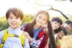 Multi-etnische groep schoolkinderen in park stock foto's