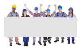 Multi-etnische handarbeiders die lege banner houden stock foto