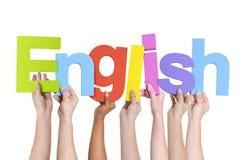 Multi-etnische Handen die het Woord het Engels houden stock foto's