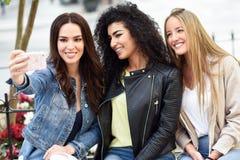 Multi-etnische jonge vrouwen die een selfiefoto samen nemen stock afbeelding