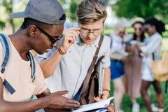 Multi-etnische jongens die boek samen in park lezen stock foto's